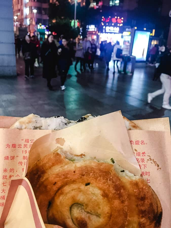 Green onion pancake in a brown paper wrapper on Nanjing Road in Shanghai, China