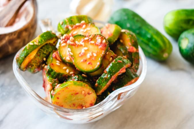 Cucumber kimchi with red Korean chili flakes and sesame seeds in glass dish.