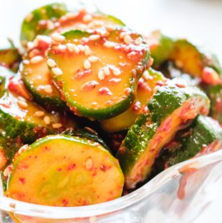 Glass bowl of sliced cucumber kimchi with sesame seed garnish