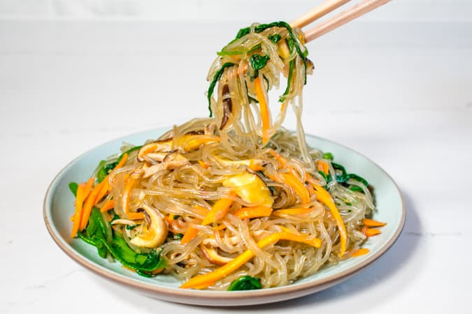Korean vegan sweet potato noodles and vegetables with chopsticks.