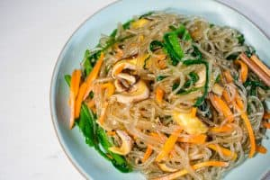 Vegan Korean glass noodles vegetarian on round blue plate.