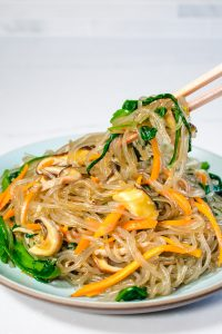 Korean glass noodle stir fry with vegetables on round blue plate with chopsticks.