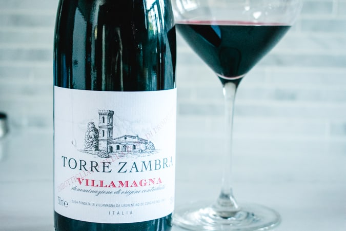 Bottle and glass of Torre Zambra Montepulciano d'Abruzzo wine on a gray background