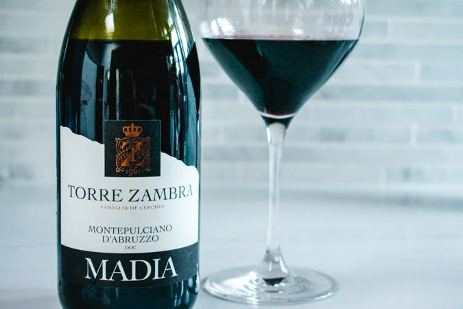 Bottle and glass of Torre Zambra Madia wine on a gray background