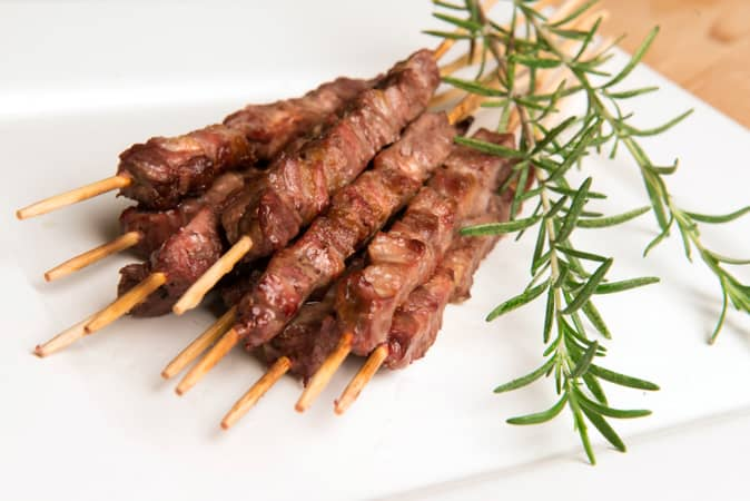 Italian lamb skewers on a white plate with sprigs of rosemary