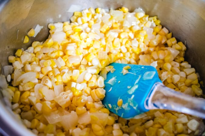 Fresh corn sauteeing in a pot with a blue spatula