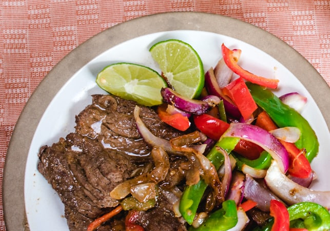 plate of carne asada, bell peppers and lime wedges