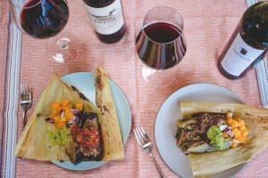 2 opened tamales with 2 glasses and bottles of merlot on red tablecloth