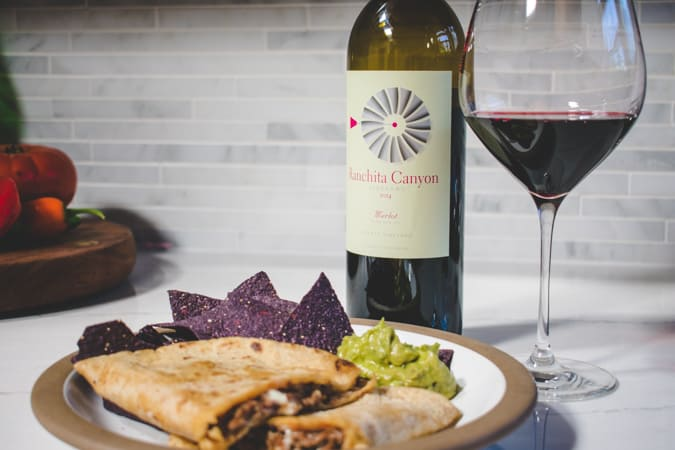 Ranchita Canyon Merlot in back of a plate of beef empanada