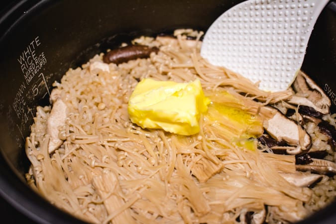 Rice cooker filled with mushroom rice, butter, and spatula