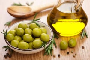 Small plate of green olives and glass pitcher of olive oil