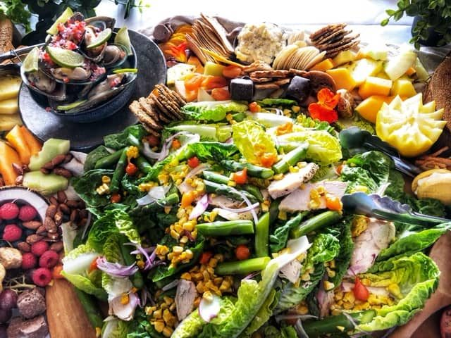 Spread of romain salad, mussles, crackers, and cheese