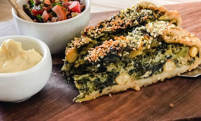 2 slices of kale pie on a wooden cutting board