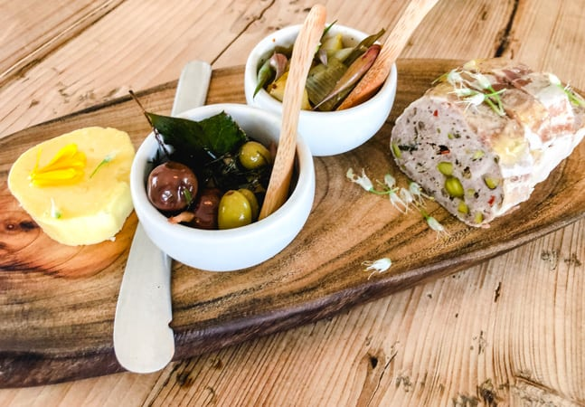 cultured butter, olives, and pate on a wooden board