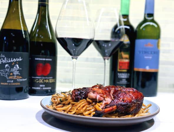 Plate of Chinese roast duck noodles with 4 bottles of French Malbec in the background and 2 wine glasses