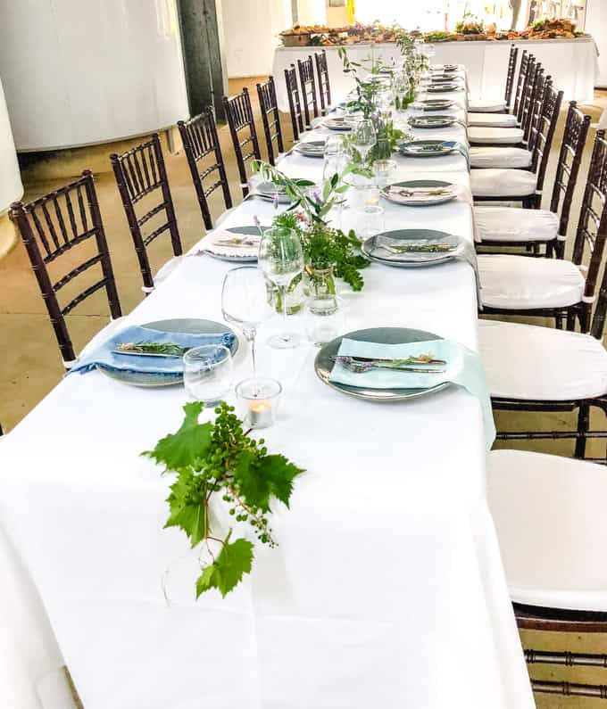 Long white table with dining chairs at Sirromet Winery