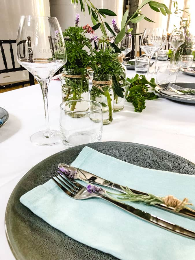 White tablecloth with dinner plate, silverware, and glass settings