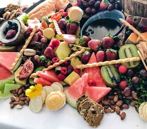 Assorted fruit, breadsticks, and chocolate sauce on a grazing table