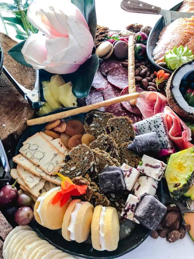 Desserts, crackers, fruit, and salami on a grazing table
