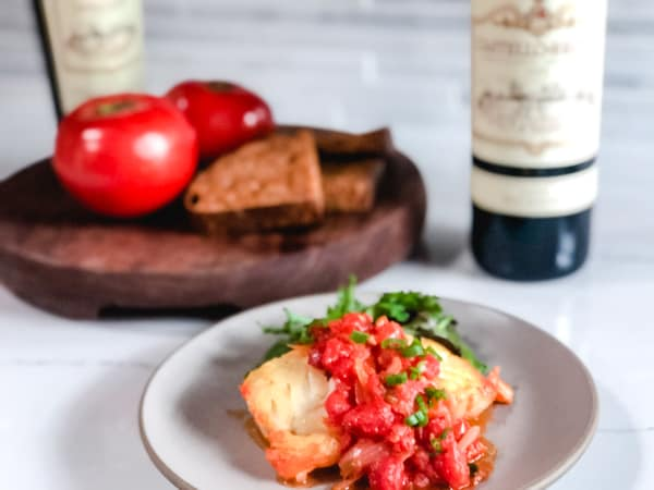 Pan Fried Cod with Vietnamese tomato sauce with wine and cutting board in the background