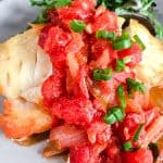 Vietnamese Fried Fish with Tomato Sauce on a gray plate with salad greens
