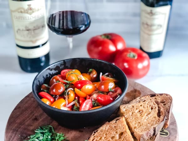 Marinated asian tomato salad with bread and chianti wine in the background