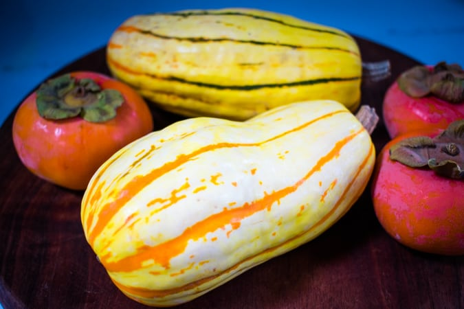 Two Delicata squash and 3 persimmons