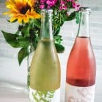 2 bottles of Petillant Naturel wine from Gilbert wine with flower bouquet in the background
