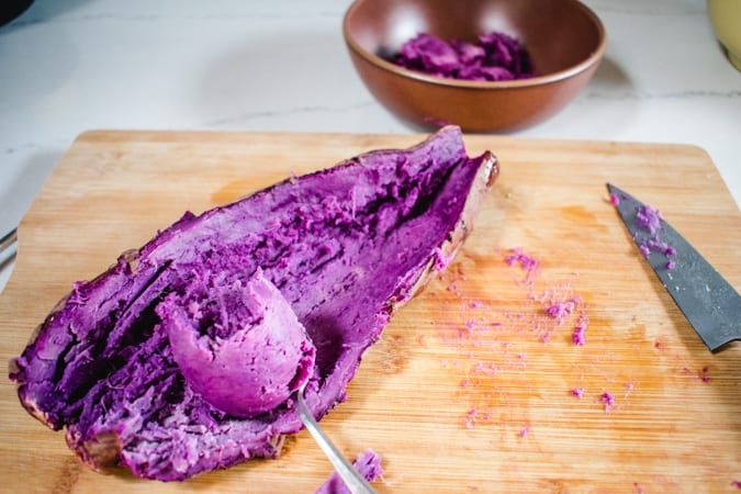 Roasted ube with flesh being scraped out