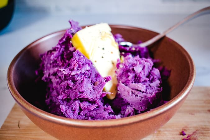 Ube mash in a brown bowl with a pat of butter