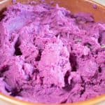 Mashed purple yam in a brown bowl with a spoon