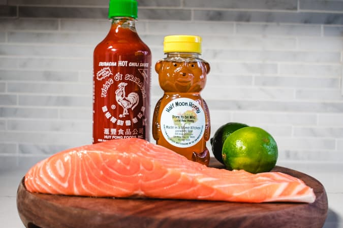 salmon fillet with sriracha bottle, honey bear, and limes