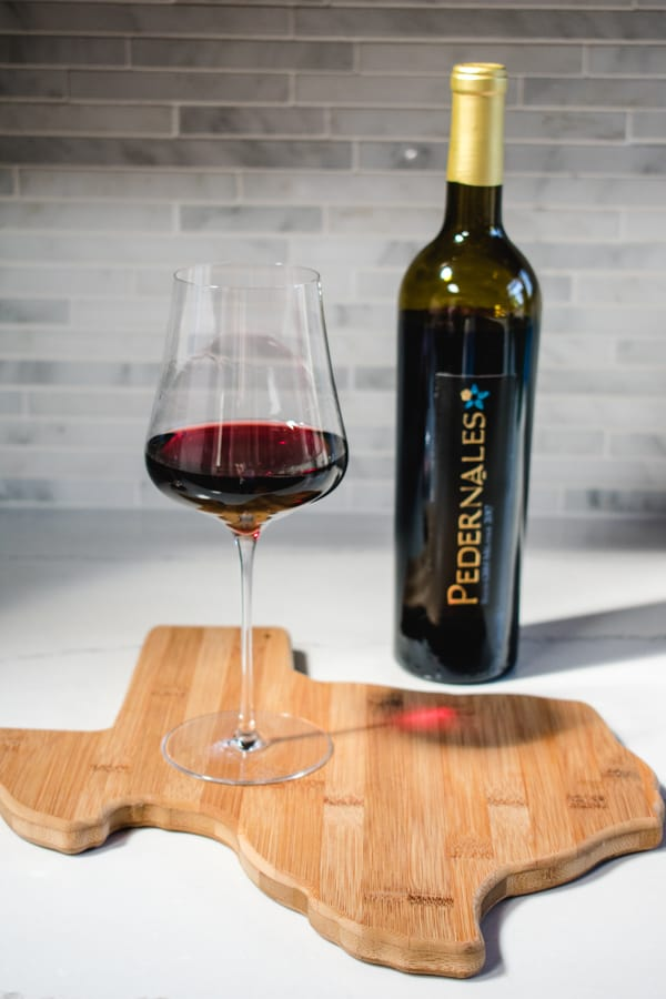 Glass of Pedernales Cellars GSM wine on a Texas shaped cutting board