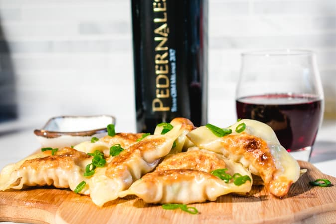 Cutting board with potstickers and Pedernales Cellars GSM wine in the background