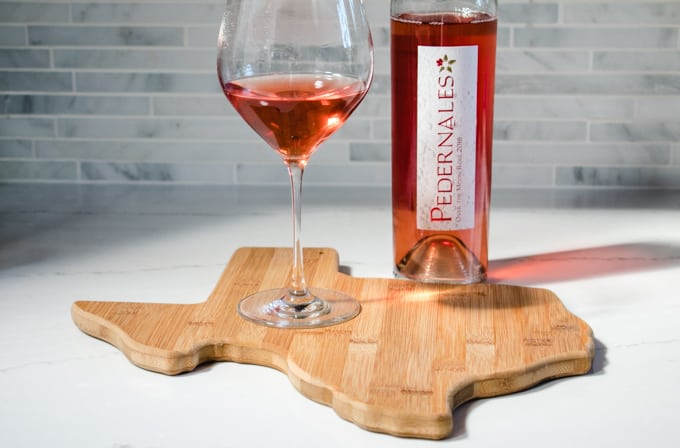 Glass and bottle of Pedernales Cellars rose on a Texas shaped cutting board