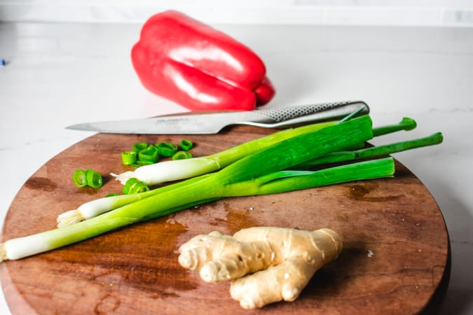 bell pepper, green onion, and ginger on a round cutting board