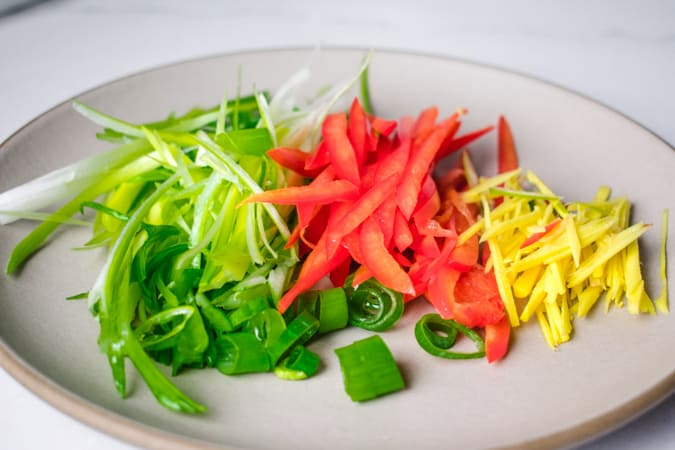 sliced green onion, red bell pepper, and ginger on a beige round plate
