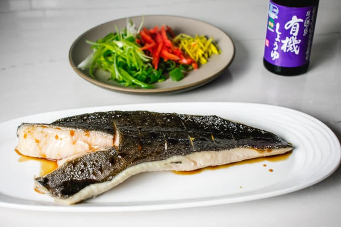 black ling cod fillet on white plate with soy sauce