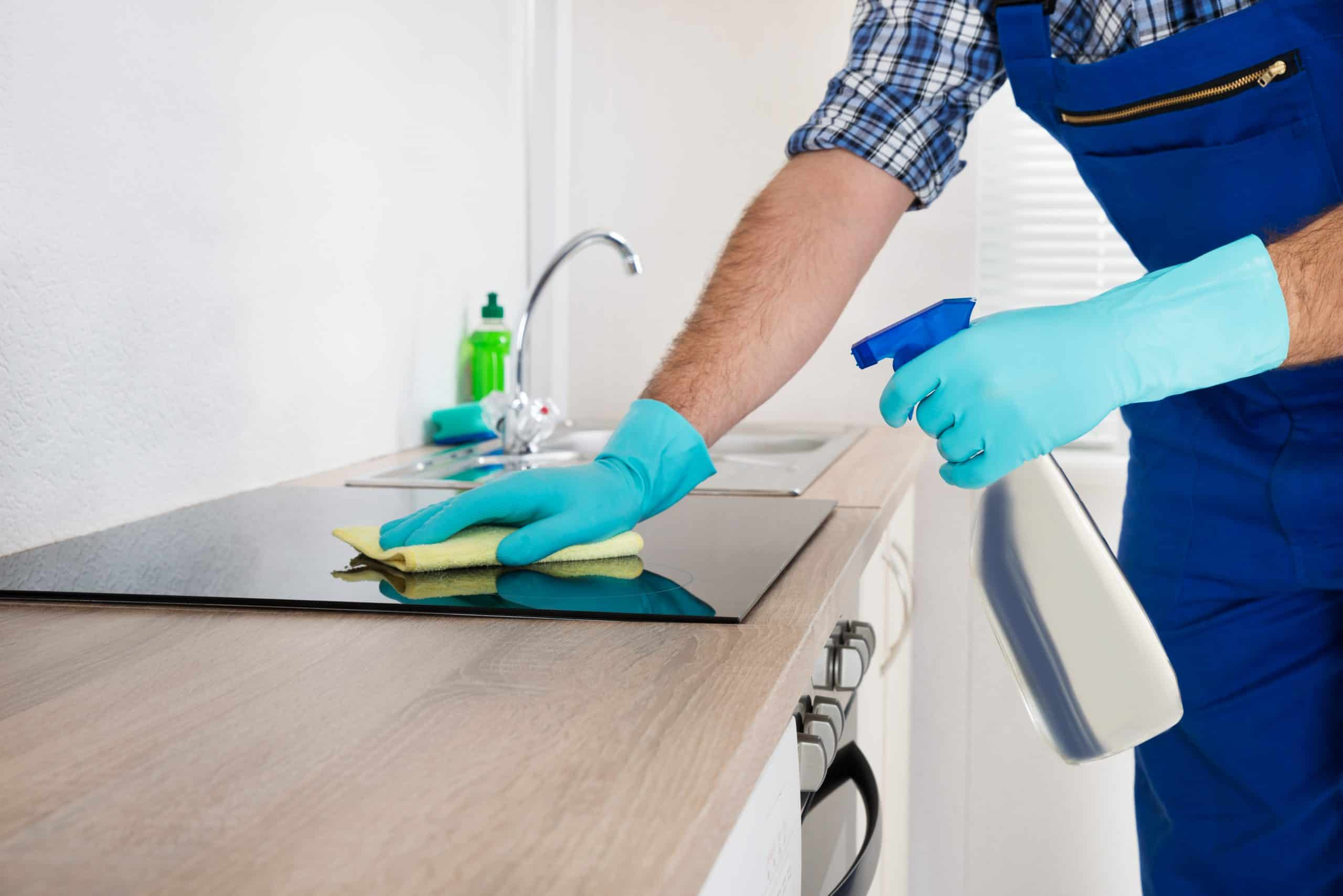 man with blue gloves cleaning the stove top