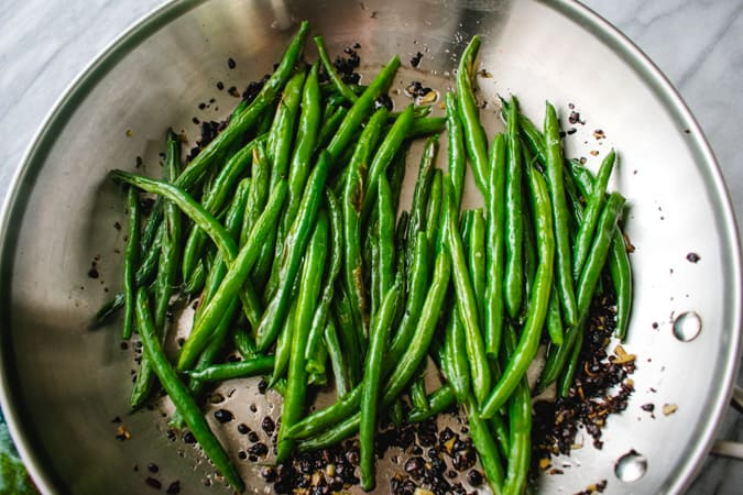 roasted green beans in skillet with Chinese fermented black beans