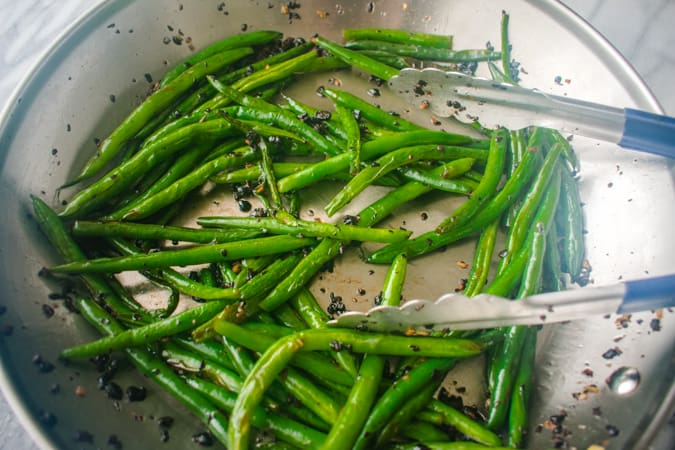 green beans with black beans in a skillet with tongs