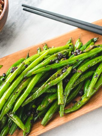 Chinese blackened green beans on wooden plate with black chopsticks