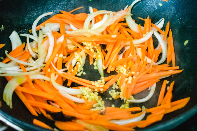 carrot, onion, and ginger in a black wok