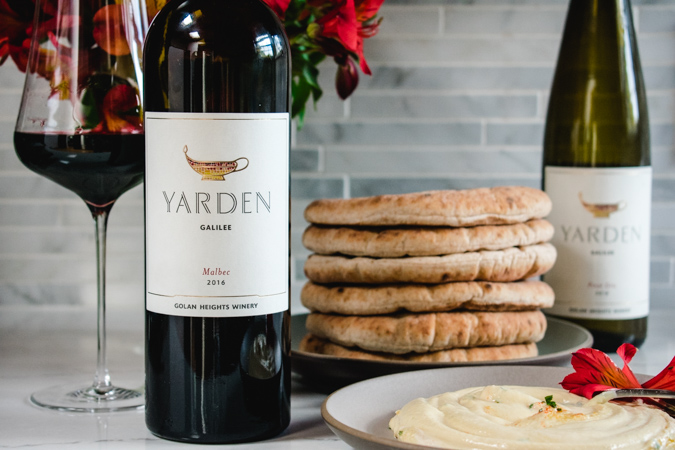 Yarden wines with a stack of pita bread and hummus