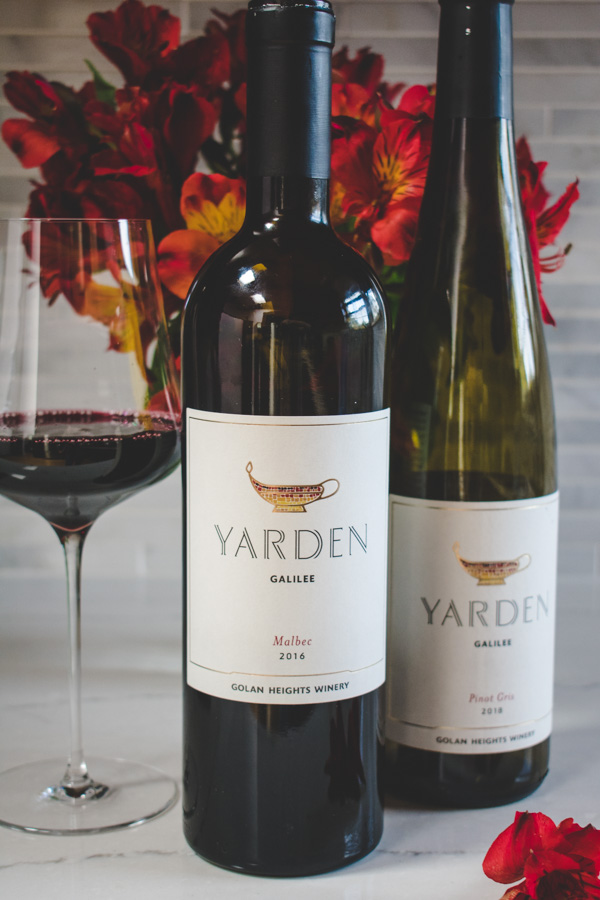 2 bottles of Yarden Wine with red flowers in the background