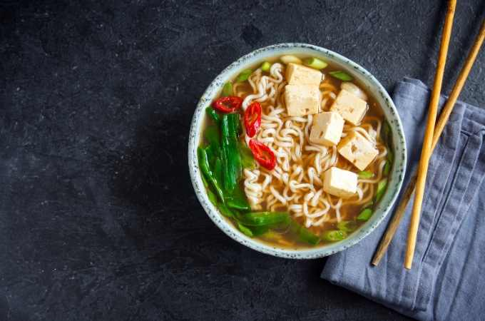 bowl of tofu ramen on a black background with