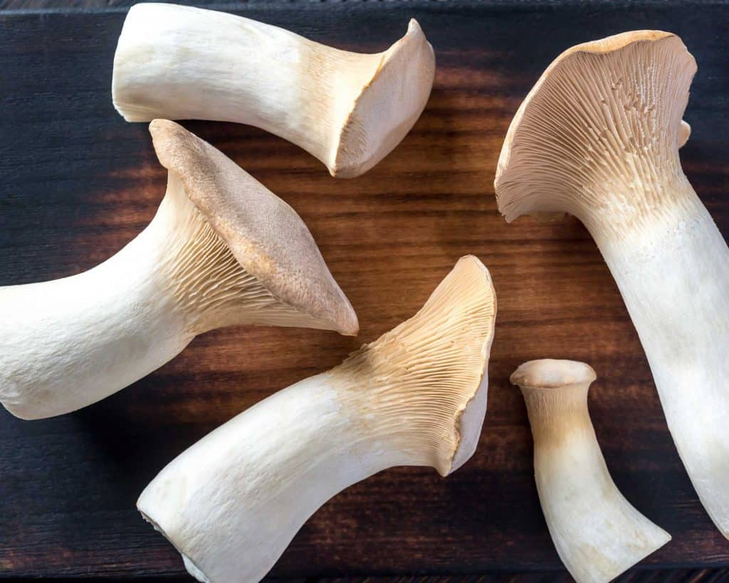 5 king oyster mushrooms on a wooden board
