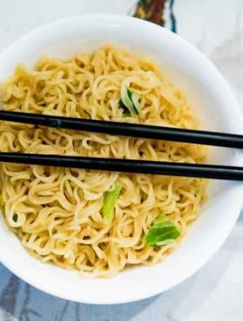 ramen noodles in a white bowl with black chopsticks