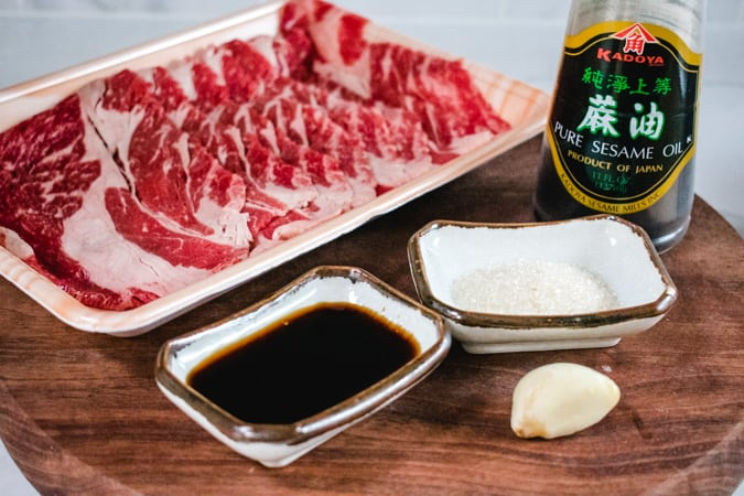 sliced beef, soy sauce, sugar, garlic, and sesame oil on a wood cutting board