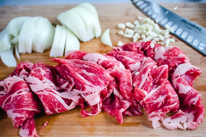 sliced beef, onion, and garlic on a wooden cutting board